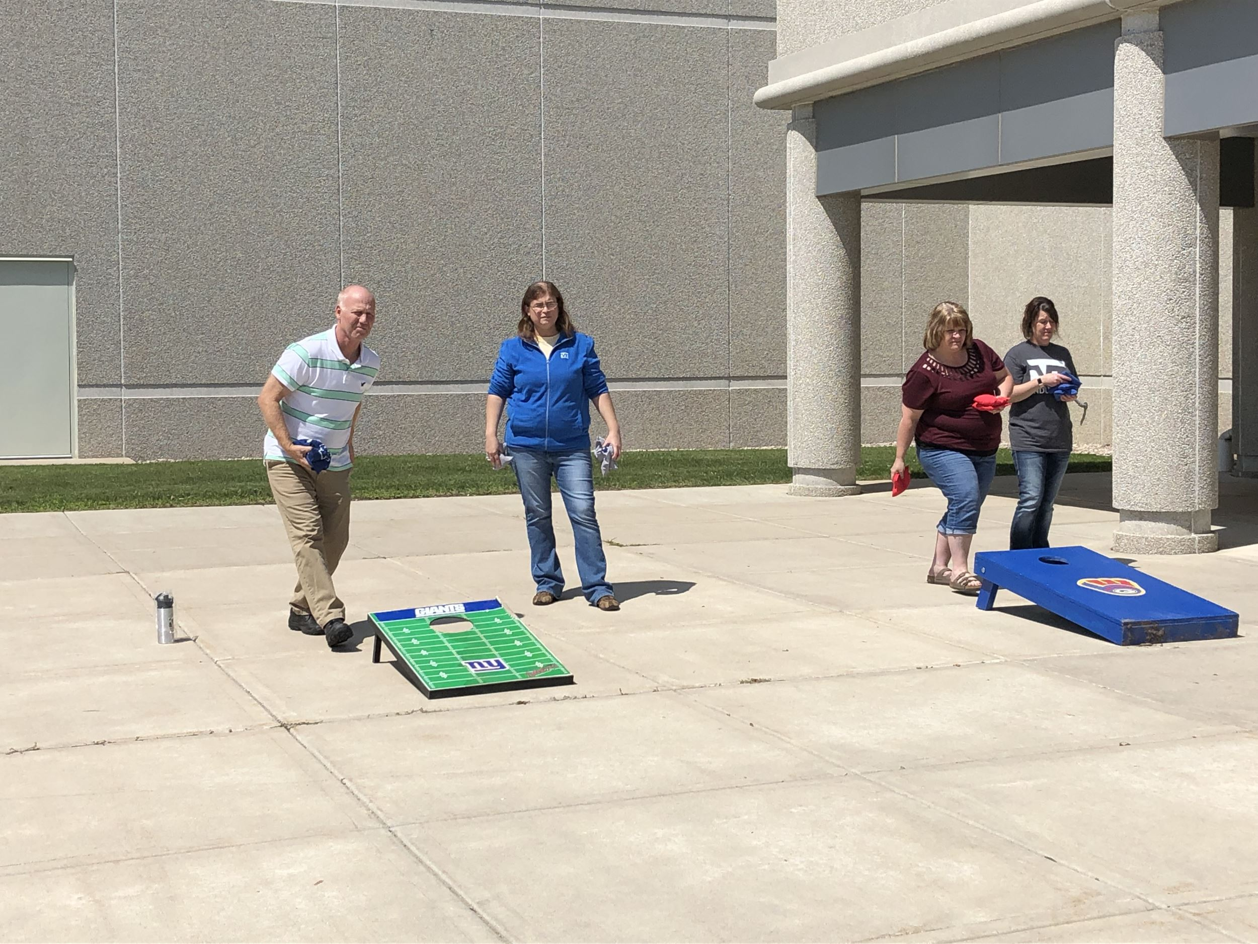 Employees playing a friendly game of bags